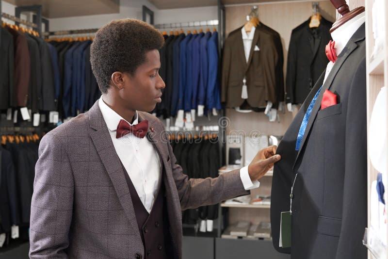 Position d'homme dans le magasin avec l'habillement près du mannequin photographie stock libre de droits