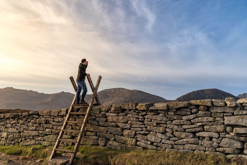Position d'homme de Moyen Âge sur l'échelle sur le mur en pierre en montagnes, recherchant dans la distance, coucher du soleil da photos stock