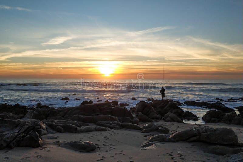 Position d'homme de silhouette sur la pêche de roche avec la tige au coucher du soleil sur la plage photos stock