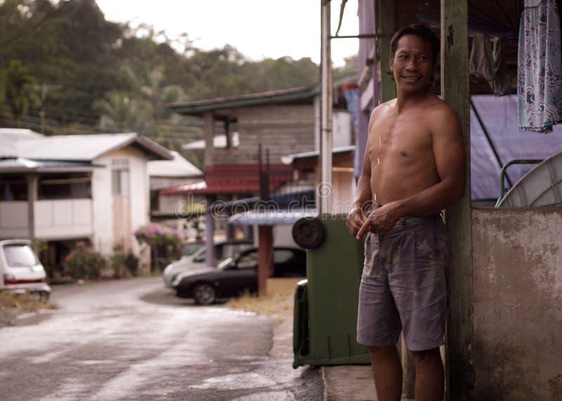 Position d'homme de village devant sa maison de Kuching, Malaisie photo libre de droits