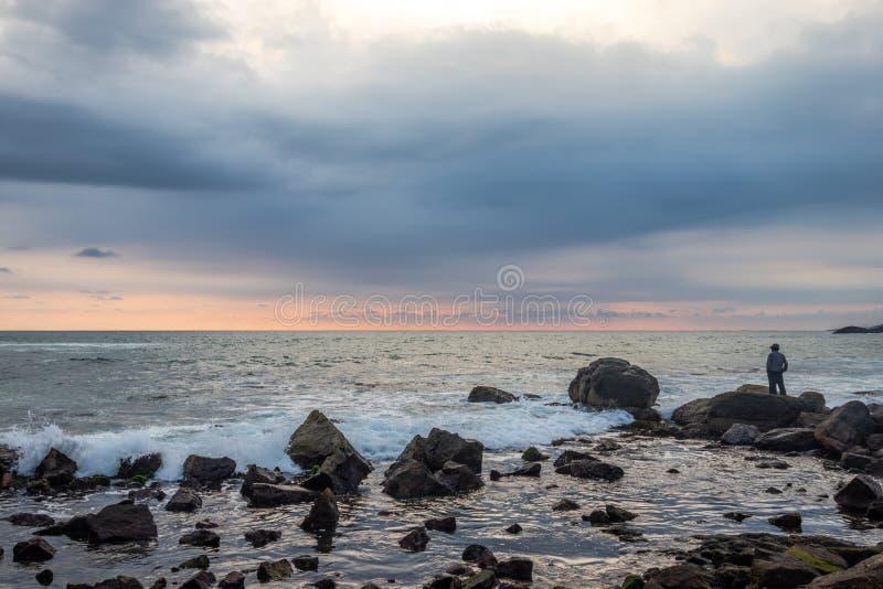 Position d'homme d'isolement observant l'horizon de mer images libres de droits