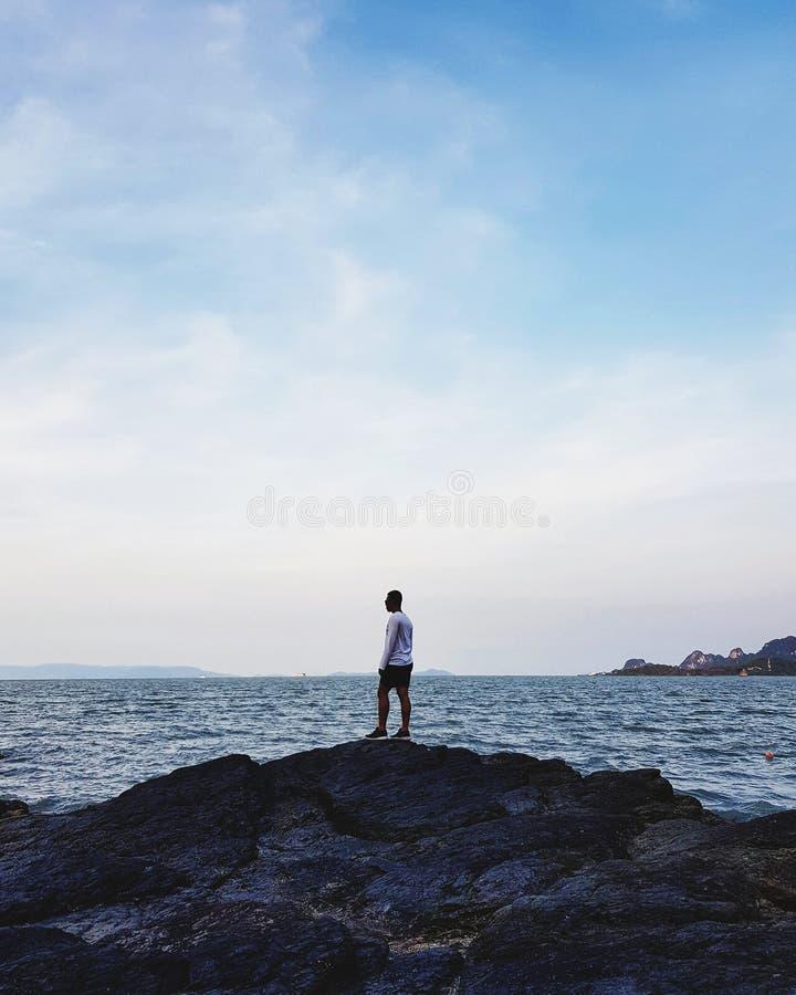 Position d'homme sur la pierre au littoral image stock