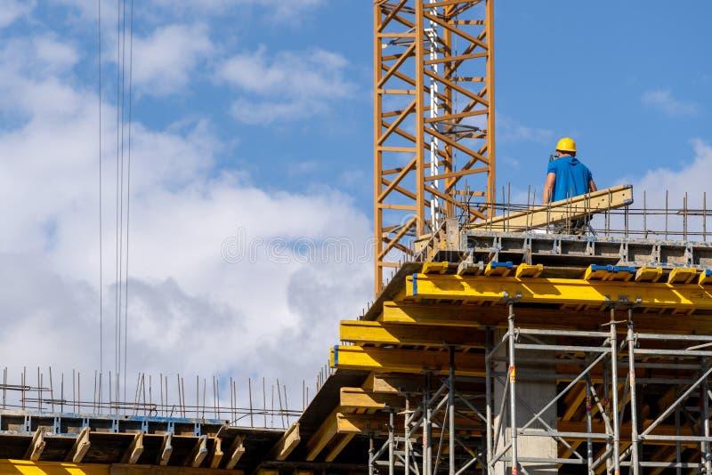 Position d'homme sur le bâtiment avec les éléments de fer et l'arpenteur de regard image stock