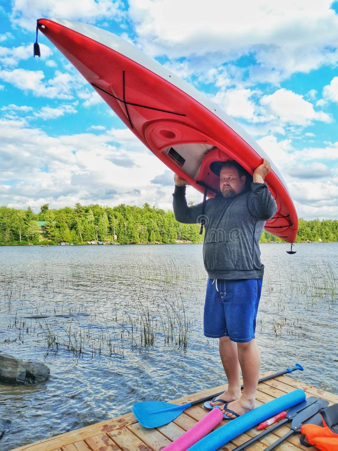 Position d'homme sur le dock en bois de rivière de lac et tenir le bateau de kayak sur sa tête image libre de droits
