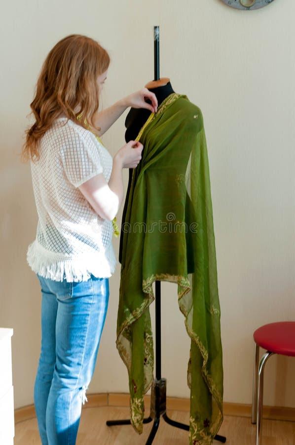Position d'ouvrière couturière près de mannequin et de tissu de mesure dans le studio de couture photo stock