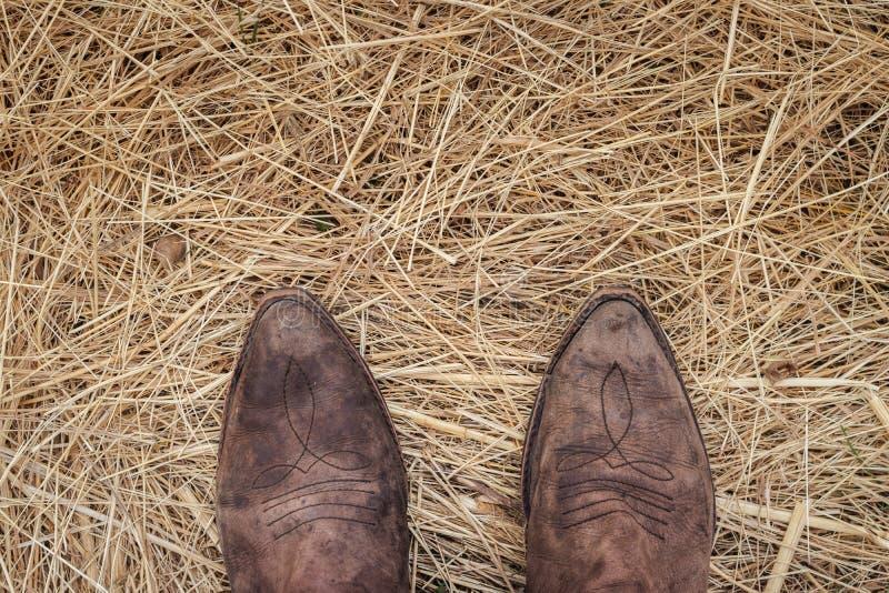 Position dans des bottes de cowboy sur le foin d'or photos libres de droits