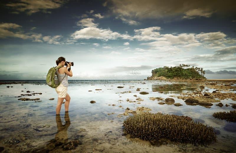 Position dans la femme de voyageur d'eau de mer avec le sac à dos prenant a photos stock