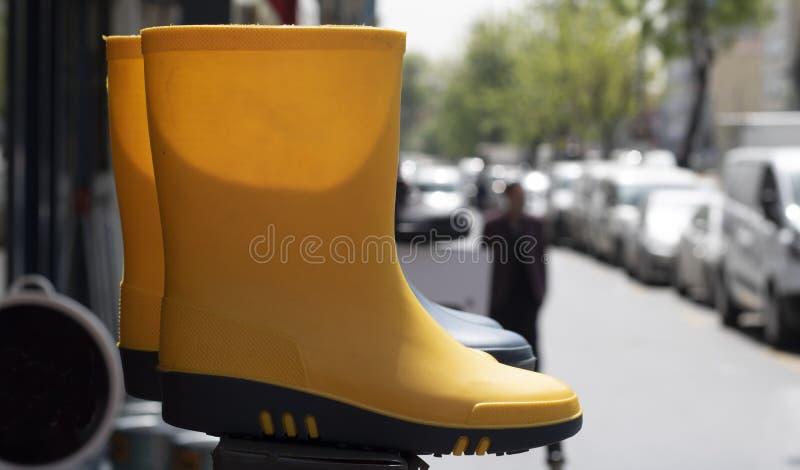 Position de banc sur le trottoir Bottes jaunes dessus photo stock