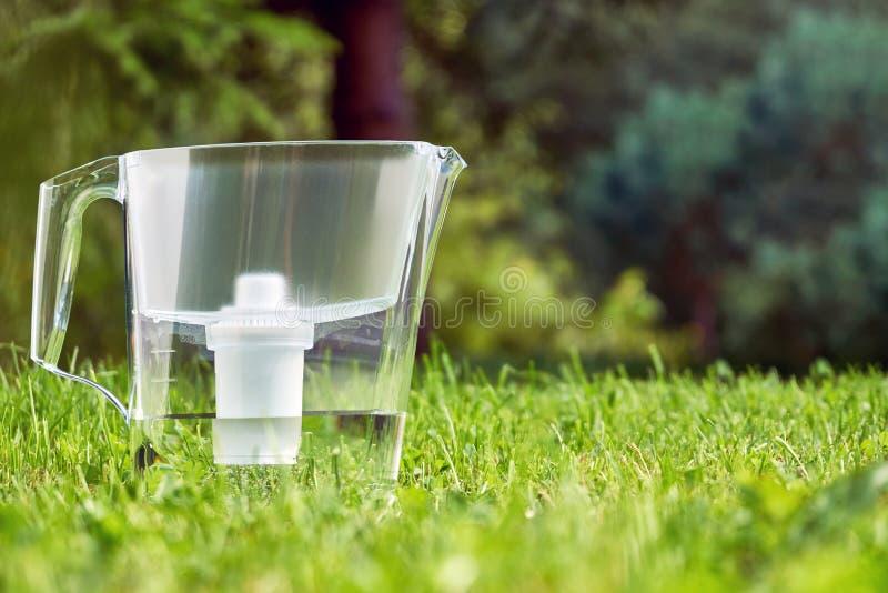 Position de broc de filtration de l'eau sur l'herbe verte dans le jardin d'été photos libres de droits