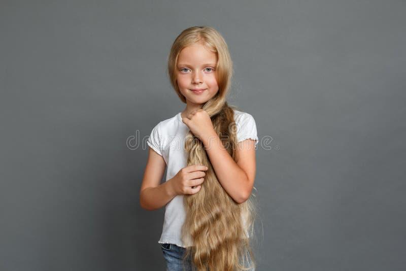 Position de cheveux de participation de petite fille longue localisée sur la pose grise dans le calme de caméra photos stock