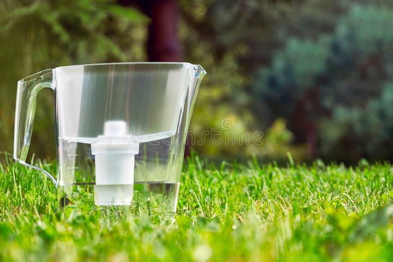 Position de cruche de filtre d'eau sur l'herbe verte dans le jardin d'été photo stock
