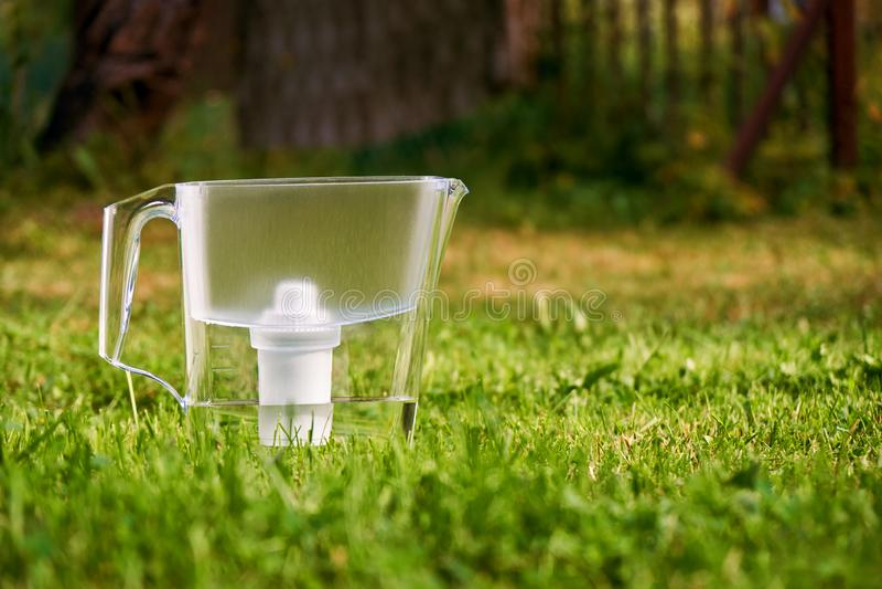 Position de cruche de filtre d'eau sur l'herbe verte dans le jardin d'été images libres de droits