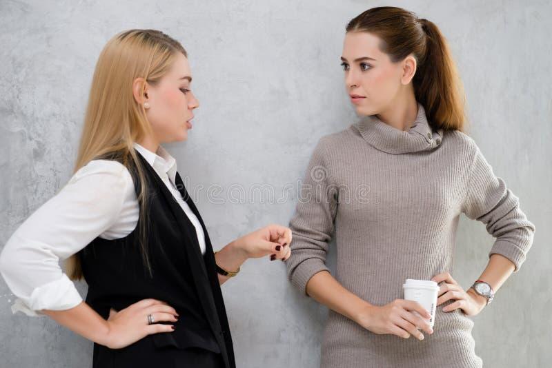 Position de deux amies de femmes élégantes parlant heureusement contre le grenier photos libres de droits