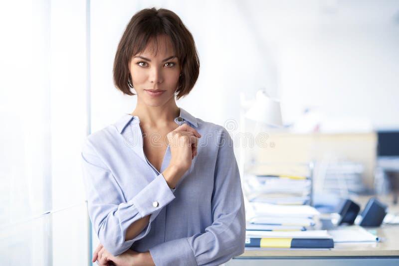 Position de femme d'affaires d'Attracive avec les bras pliés dans le bureau image stock