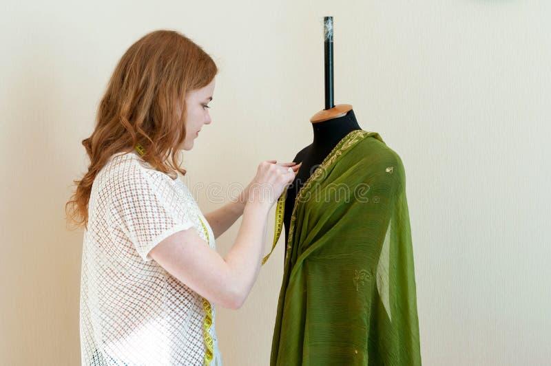 Position de femme près de mannequin et de tissu noirs de mise image stock
