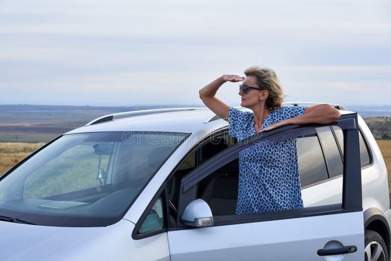 Position de femme se penchant sur une porti?re de voiture photo libre de droits