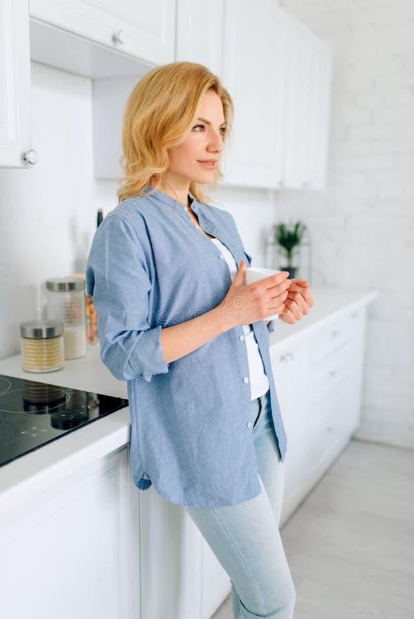 Position de femme sur la cuisine avec l'int?rieur blanc comme neige images libres de droits