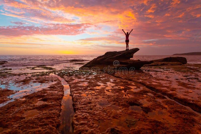 Position de femme sur les roches côtières avec le lever de soleil et les réflexions renversants photographie stock libre de droits