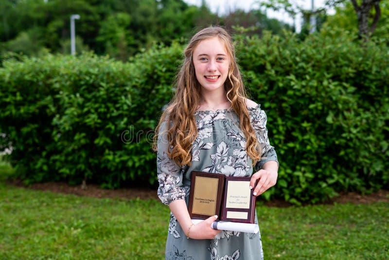 Position de fille de jeune adolescent/d'étudiant collège devant un buisson/jardin après sa cérémonie tout en tenant un diplôme et photo stock
