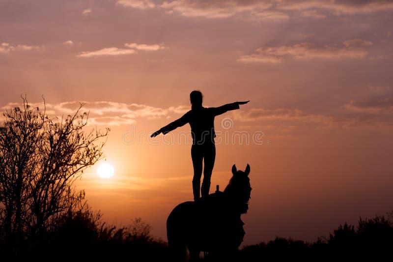 Position de fille sur un cheval avec les mains augmentées au côté comme une aile d'avion photos libres de droits