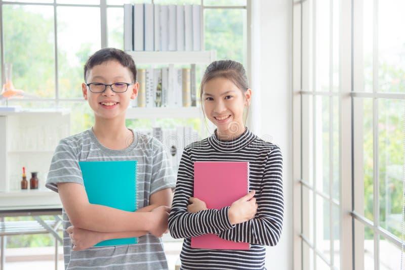 Position de garçon et de fille et sourire dans la salle de classe photos libres de droits