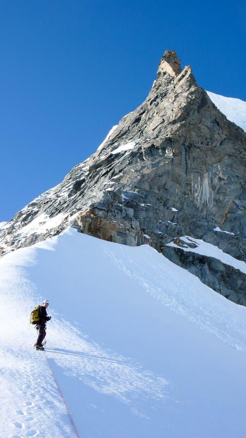 Position de grimpeur de montagne sur une arête de neige et de glace au-dessous d'une crête de montagne pointue d'aiguille de roch photos stock