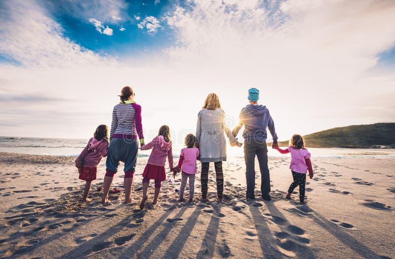 Position de groupe de famille et d'amis sur la plage tenant des mains photos stock