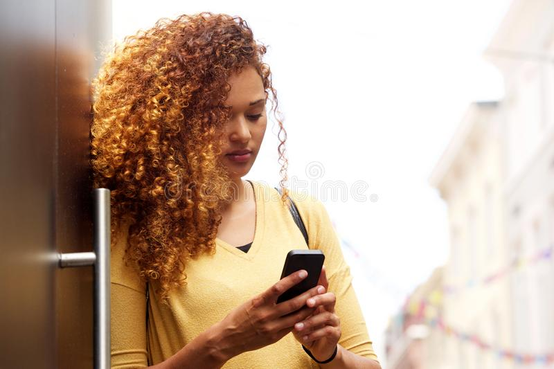 Position de jeune femme avec le téléphone portable dans la ville photo stock