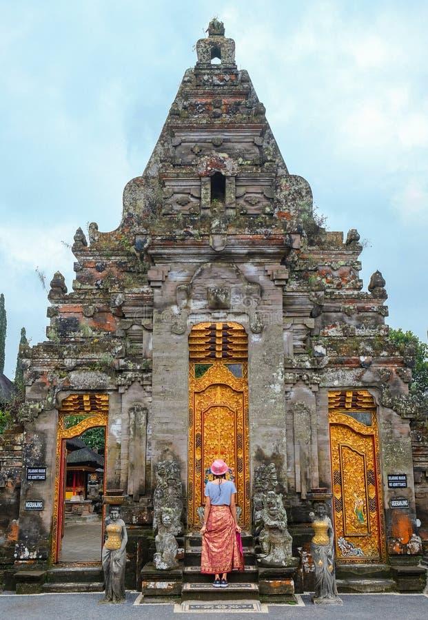 Position de jeune femme devant la porte de Pura Ulun Danu Bratan, un temple hindou, un de l'attraction touristique célèbre dans B photographie stock libre de droits