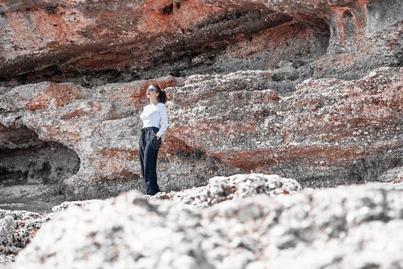 Position de jeune femme sous la falaise Voyageur et blogger images stock