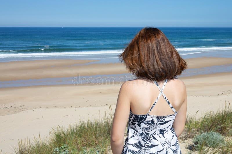 Position de jeune femme sur une plage regardant à l'horizon photos stock