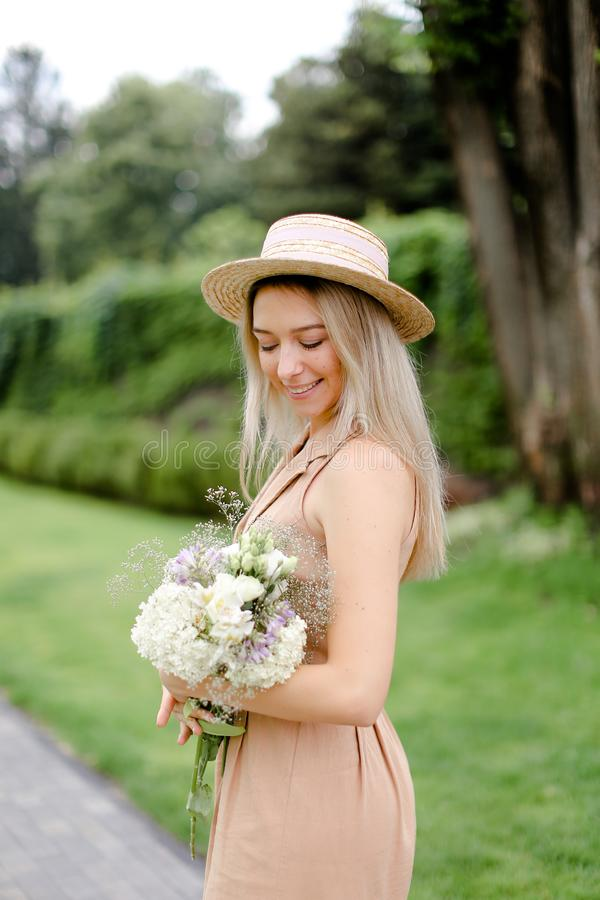 Position de jeune fille dans le yeard avec le bouquet des fleurs et du chapeau de port images stock