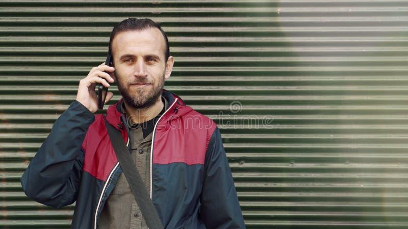 Position de jeune homme contre un fond de mur et un smartphone d'utilisation images stock