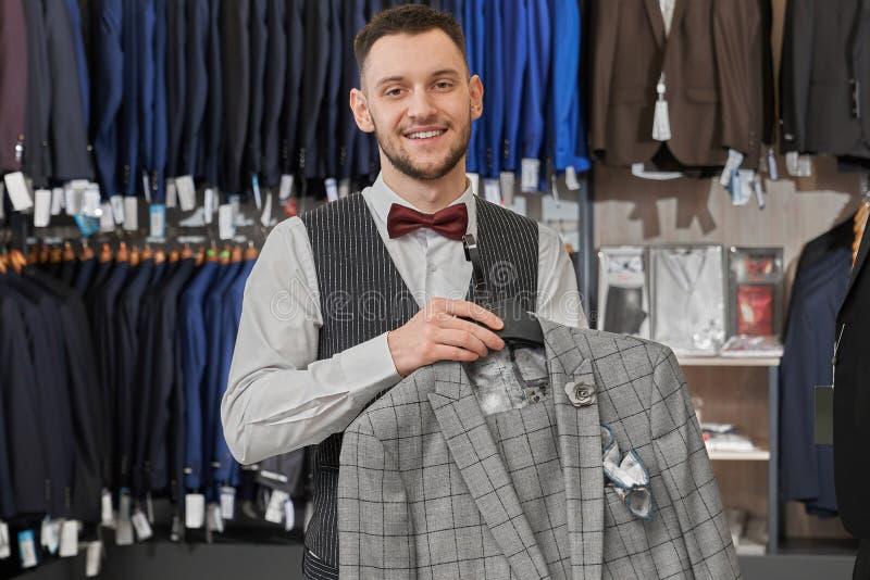 Position de jeune homme dans la boutique, tenant la veste sur le cintre photo stock