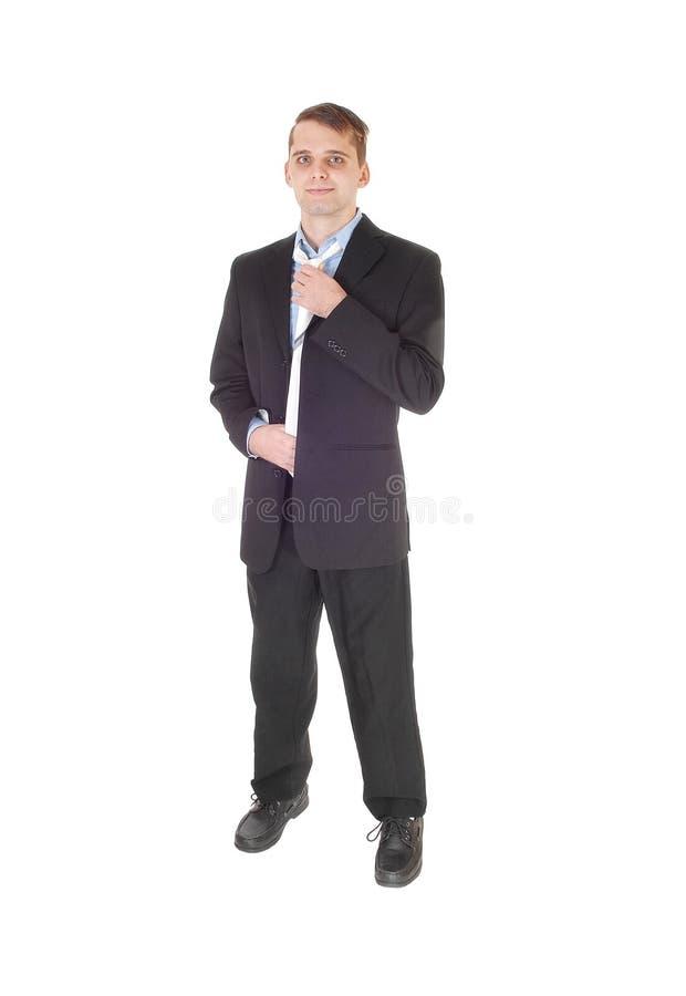 Position de jeune homme dans un costume fixant son lien photos stock