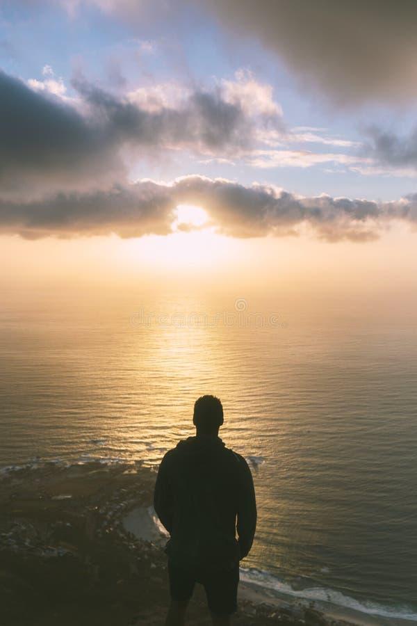 Position de jeune homme sur le bord en haut de la montagne principale du lion à Cape Town image stock