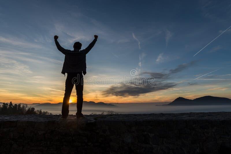 Position de jeune homme sur un vieux mur sous le ciel égalisant glorieux photos libres de droits
