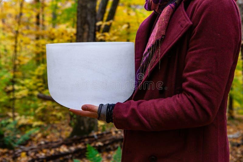 Position de jeune homme tenant sa cuvette en cristal solennellement dans la forêt 1/4 image stock