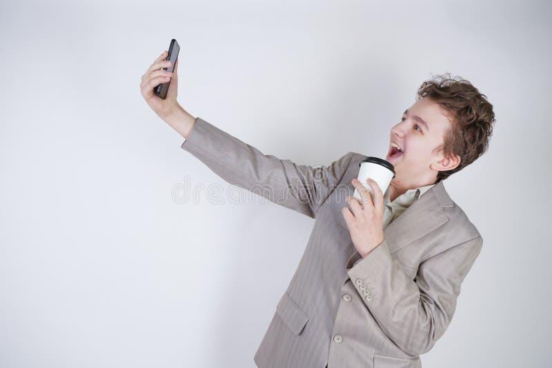 Position de l'adolescence émotive drôle de garçon avec la tasse de papier de thé et de selfie de faire sur seul le fond blanc images libres de droits