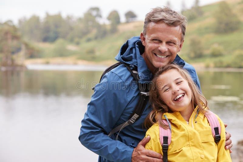 Position de la préadolescence caucasienne de fille avec son père sur le rivage d'un lac, riant de la caméra, fin  images libres de droits