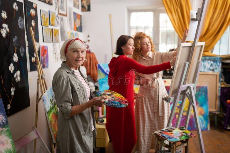 Position de mélange de gouache de professeur d'art près des étudiants photos stock