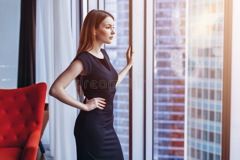 Position de pensée de femme attirante aisée au paysage urbain admiratif de fenêtre en son appartement d'appartement terrasse image stock