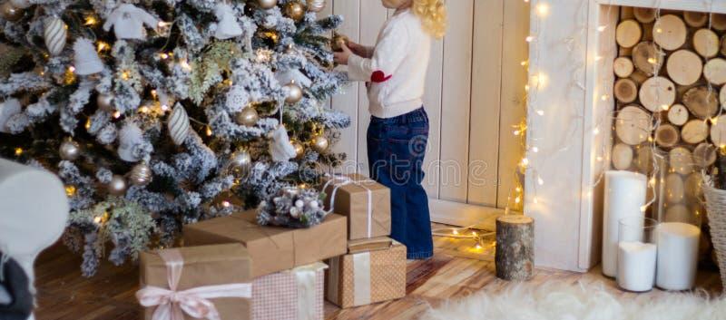 position de petite fille près de l'arbre de Noël, nouvelle année présents images stock