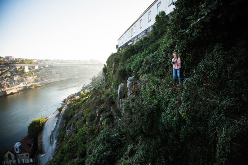 Position de photographe de jeune femme sur une roche verte devant la rivière de Douro, Porto photographie stock