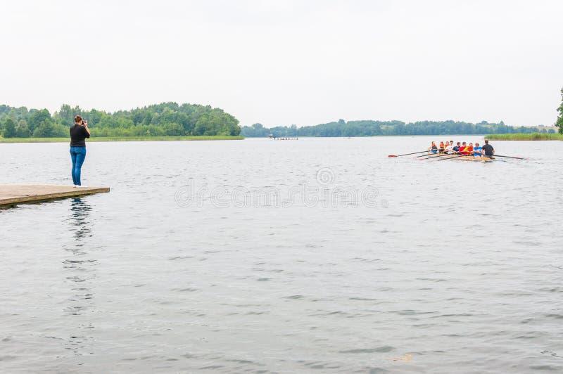 Position de photographe sur le pilier et les images de fabrication d'un bateau à rames huit de flottement avec les touristes et l images stock