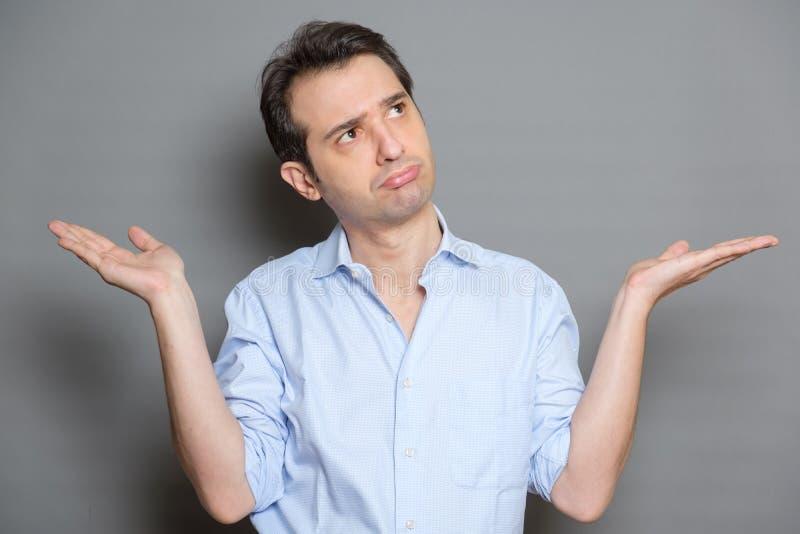 Position de port de chemise d'homme confus et gesticulation au-dessus du fond gris images libres de droits