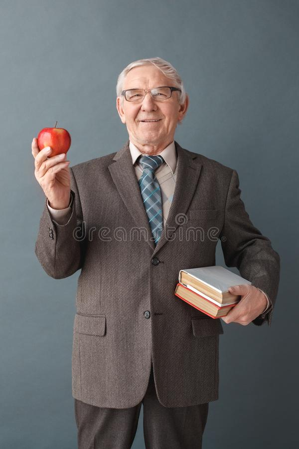 Position de port de studio en verre de professeur d'homme supérieur d'isolement sur le gris avec les livres et la pomme regardant photos stock