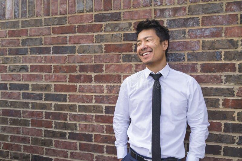 Position de sourire d'homme d'affaires asiatique à côté du mur de briques photos libres de droits