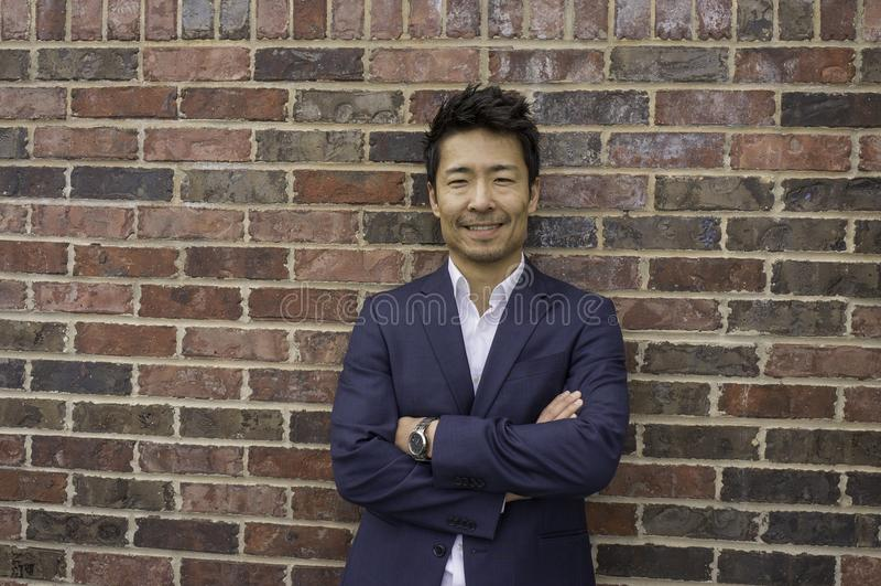 Position de sourire d'homme d'affaires asiatique à côté du mur de briques photo libre de droits