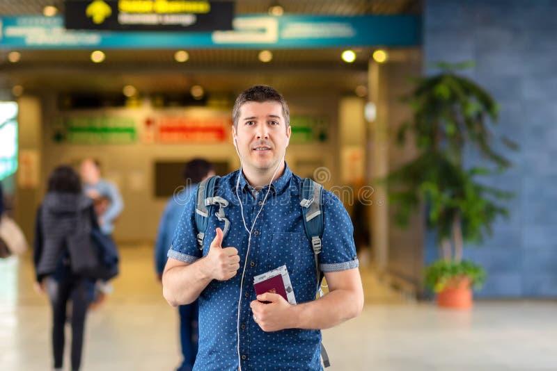 Position de sourire d'homme au passeport et à la carte d'embarquement modernes de participation de terminal de départ d'aéroport photos libres de droits